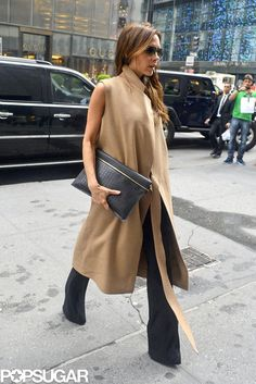 Victoria Beckham in black flare pants with sleeveless tan coat and black clutch.
