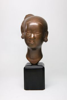 This bust is quite heavy. The face features a female figure with pierced ears and her hair tied up in a bun. The metal is non-magnetic. It is polished and unpainted.  The entire piece stands 11 1/2 inches tall and the base is 3 inches across. The face is a little over 4 inches in width.