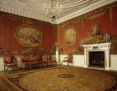 "Designed for the Earl of Coventry by Robert Adam, the room features walls lined with tapestries and similar-looking upholstery. A novel aspect is the continuous tapestry on all four walls, in effect a pictorial wall covering rather than a framed, painting-like tapestry. The scenes in the cartouches were designed by Boucher; the tapestries woven in Jacques Nielson's atelier at Gobelins. ""Aux alentours"" (with borders) refers to the production technique, whereby a detailed scene was fit into a plainer, more quickly executed surrounding. The Creation of Color in Eighteenth-Century Europe"