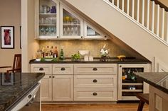 Eric created a bar with the found space under the stairs. Glass-door upper cabinets, which were custom made, mix stylistically with a glass-topped counter, 3-D glass backsplash and under-the-counter refrigerator.