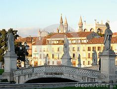 Photo made in Padua in Veneto (Italy). In the picture, taken from the south side of the big square called Prato della Valle, you see some of the statues that are disponte around the perimeter and you see one of the four bridges to cross the canal that forms the perimeter of the island Memmia. in the background you see some details, stately and historic homes in the city.