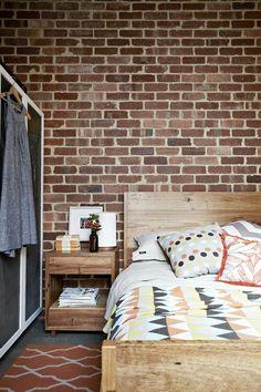 Brick wall and rustic wood bed