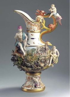A large Meissen porcelain ewer emblematic of Fire -   CIRCA 1880, BLUE CROSSED SWORDS MARK, INCISED 310., PRESSNUMMERN, RED 26. -   After a model by J.J. Kaendler (1741), with dragon handle surmounted by a fire-carrying putto, the body raised with an erupting volcano and wild animals escaping from a forest fire, a figure of Vulcan carrying bellows seated on the shoulder and a fire-bearing youngster to the side, the foot with another putto (restored extremities and chips)  65.5 cm. high