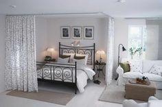 estudio open space com cama separada de zona de estar por cortina