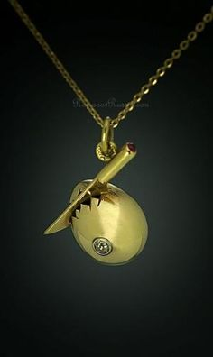 Antique Faberge pendant in the form of a gold egg being cracked with a knife…