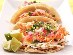 CRUNCHY FRIED FISH TACOS Ingredients 1 1/2 cups cake flour 2 tablespoons chili powder 2 teaspoons black pepper Kosher salt 3/4 cup beer 1 egg 3/4 cup mayonnaise 2 tablespoons sriracha 2 quarts peanut oil 1 pound white fish 16 corn tortillas, warmed 1 small head of cabbage, finely shredded pickled red onions cilantro 2 limes
