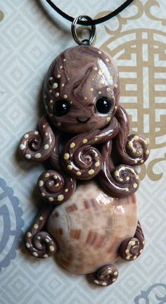 An octopus pendant made from polymer clay and a calico scallop shell.