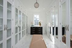 Luxurious walk in closet with white mirror cabinets marble floor and pendant light