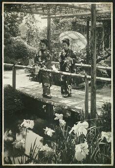 Two women on a bridge in a garden: Geishas in the garden of a tea house, Japan.