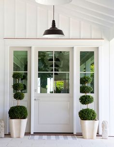 Modern farmhouse side door with hanging pendant light and trimmed boxwood topiaries.