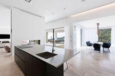 carrelage grand format en gris, îlot de cuisine en noir, faux plafond design avec spots à LED intégrés et suspension design