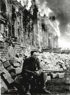 Defeated German soldier in front of burning Reichstag, Berlin, 1945.