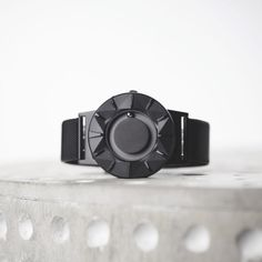 The Bradley Element by Eone features a scratch-resistant ceramic case with black PVD coating. The watch face contours toward each marker in alternating concave and convex forms. Like the original Bradley, it has an adjustable black Milanese mesh strap. #watches #design