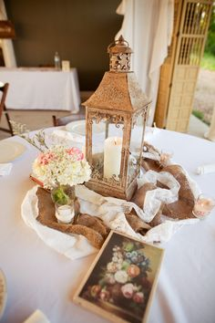 lantern with draping flower/vine, like the fabric around lantern, maybe use wood to place Bible verses on table, use antique Bibles to sit lantern on?
