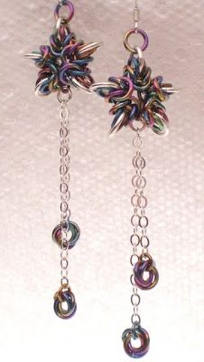 An array of colorful anodized niobium rings, with sterling silver rings marking each point, and sterling silver chains trailing underneath. Based on the classic Byzantine pattern, arranged by 5 into a star shape, together with the long dangles.The earrings measures at 2 1/2 inches long from the bottom of the sterling ear wires, 3/4 inch wide from point to point of the stars, and are made entirely of sterling silver and anodized niobium. The stars are solid but still light weight.