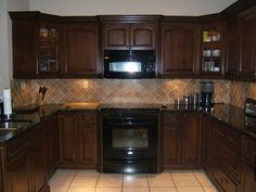 cherry cabinet, dark granite, light backsplash in nice pattern, light tile floor