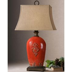 Traditionally inspired, this table lamp is made of crackled red ceramic with rust brown details. The rectangle bell shade is a rust linen fabric with natural slubbing.