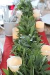 A Christmas tablescape using fresh bay leaves, metallics, and natural wood. Olive branch swag across each chair and sparkling lights add festive touches.