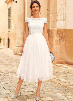 Kaleidoscope Tulip Bardot Midi Bridal Dress. Team traditional styling with on trend looks and you get this beautiful bardot-style prom wedding dress. Simple in design, with an elegant wide textured bardot band and fitted bodice with a pinched-in waistband. The dramatic mesh layered skirt completes the look. This dress carves a beautifully feminine shape. {affiliate link} #bridalgown #weddingdress