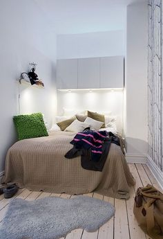 Small bedroom inspiration: add storage over the bed and hang lighting underneath it.  Also paint walls and ceiling one color so the eye keeps moving.  Can have an accent wall like this birch tree wallpaper.