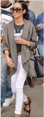 Jhene Aiko wearing white jeans, a graphic tee, and army green jacket