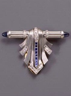Krementz & Co. - An Art Deco dress clip, Newark, New Jersey, 1925-1930. Platinum, gold, diamonds and sapphires. 1.25 x 1.25 in. #Krementz #ArtDeco #DressClip