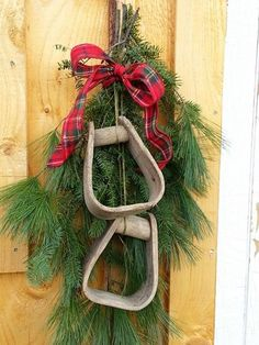Old wooden horse stirrups with fresh cut pineboughs for a holiday door swag.