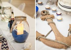 Nautical wedding details including a blue sand filled glass centerpiece and wooden anchor tied with rope.