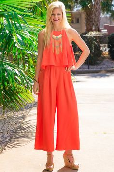 """Whether it's a country club in the states or an South American island you have in mind, this exquisite jumper will have you looking """"Isla Del Sol"""" ready to go. At a golf tournament or a day on the beach, you'll be looking grand. Wide leg jumpsuit features a halter neckline with a pleated tier overlay and a hidden zipper on the back. Model is wearing a small. • Self: 100% Tencel • Lining: 100% Rayon • Hand Wash Cold • Fully Lined • Faintly Sheer"""
