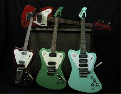 3 Gibson Firebird guitars, with a Thunderbird bass sitting on the Magnatone amp behind them.