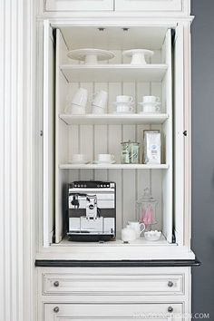 Small appliance cabinet to conceal coffee maker and breakfast essentials.  Pocket doors slide out of the way.  Clive Christian cabinetry.  Designed by Heather Hungeling