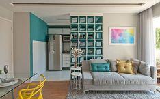 Neste pequeno apartamento em São Paulo, a designer de interiores Adriana Fontana usou uma parede com cobogós quadrados para dividir as salas da cozinha.  Fotografia: Divulgação.