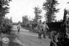 Four soldiers of the 82nd Airborne US on a road bordered by a hedge, 12 june 1944.