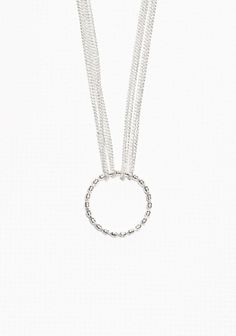 Delicate chains connected to a textured ring make this necklace both understated and chic.