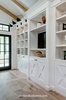 A custom media center incorporates the TV with built-in open shelves and hidden storage. Built In Wall Units, Built In Shelves Living Room, Tv Built In, Built In Bookcase, Storage In Living Room, Bookshelves, Built In Media Center, Office Built Ins, Hidden Storage
