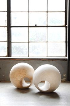 May Furniture Company Solid O.S.B. spheres.  They sit flat on the ground and  can be used as a seat or simply as a sculptural object.