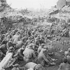 IWM caption : Crossing the Rhine 24 -31 March 1945 : Hundreds of German prisoners of war sitting together in a compound after their units had been overrun in the Allied advance. The large numbers of POWs falling into Allied hands during the final months of the campaign in North-West Europe formed a major administrative problem.