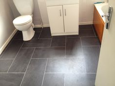 Pretty Bathroom Floor Tile Ideas in Black Color Combine with White Toilet and Cabinet