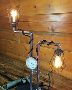"""This tall steampunk lamp is made of copper pipe, and has a beautiful aged patina. It has been fitted with a 4 inch gauge, vintage cloth covered twisted-wire and is controlled by the switch mounted on the base. The two amber Edison bulbs give off a nice warm light. (bulbs included).  The lamp is mounted on a 12"""" by 6"""" wooden base and stands 24"""" tall."""