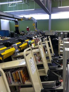 View of TechLogic sorter at Plymouth Library showing the book carts in place on sorter.  Instead of bins, items are sorted directly to the bookcarts.