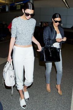 Kendall Jenner wears a gray cropped sweater, jogger pants, fancy slip-on sneakers, and a Balenciaga bag