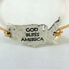 This thin gold bracelet hold a silver cutout of the United States that declares…