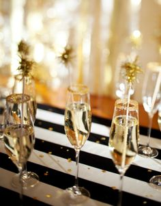Happy New Year champagne flutes with gold topped drink sticks. Black, white and gold color theme.