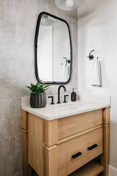 bathroom with light gray tiled walls and a brown wood vanity. White countertop and dark metallic decor. Farmhouse Exterior Colors, Painting Bathroom Cabinets, White Countertops, Wall Paint Colors, Wood Vanity, Luxury Vinyl Plank, White Houses, House Rooms, Amazing Bathrooms