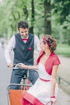 Brautpaar mit Fahrrad, Braut mit kurzem Hochzeitskleid mit roter Kante und rotem Tüll, passendes Jäckchen und Accessoires für den Bräutigam (www.noni-mode.de - Foto: Le Hai Linh)