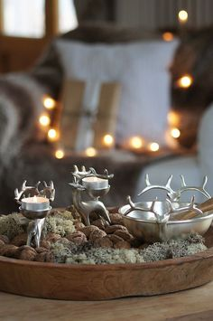 Pewter reindeer tealight holders, bowl, nuts, and moss in a wooden bowl.