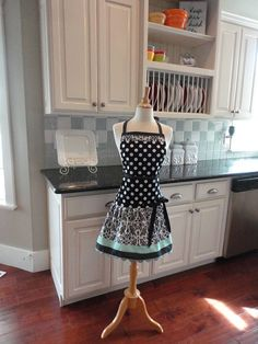 Our Cute Ellie Apron in patterns of black and white polka dots. Very cute Damask . Seaside large ric rac trim. Adorned with satin ribbon that can easily be removed.  LARGE FRONT POCKET across the front of the apron.   Ties around the neck and has wrap around belt tie to fit a variety of sizes from 4 to 14. If you need a smaller or larger size, please email for availability.  Thanks for visiting our site. Beautifully handcrafted by a mom and her daughters in a smoke-free/pet-free environm...