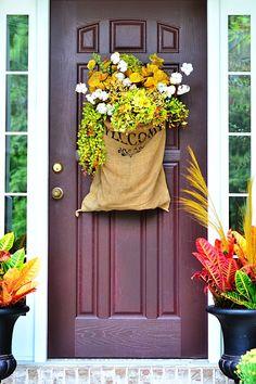 Fall front door arrangement in burlap sack