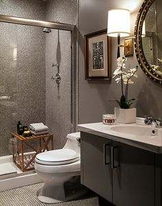 The tiny tiles echo the detail in the mirror. Pretty mirror...traditional sconces, tiny tile in both shower and on floor, art and wooden bench...and well as striking light and dark sink/floating vanity all say elegant