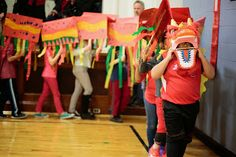 """kid-made dragon for a dragon parade! each student decorated their """"scale""""--a tent made of of three pieces of paper and two sticks."""